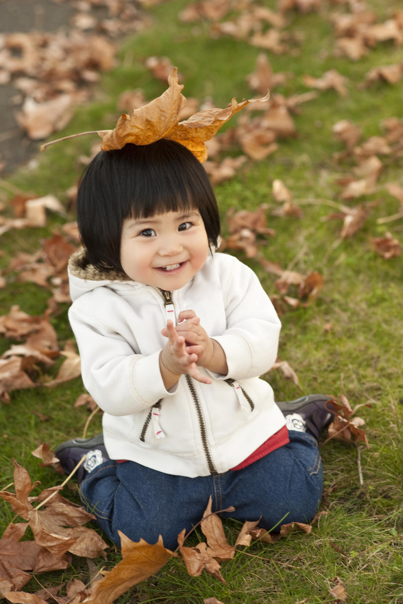 Toddler playing in fall leaves
