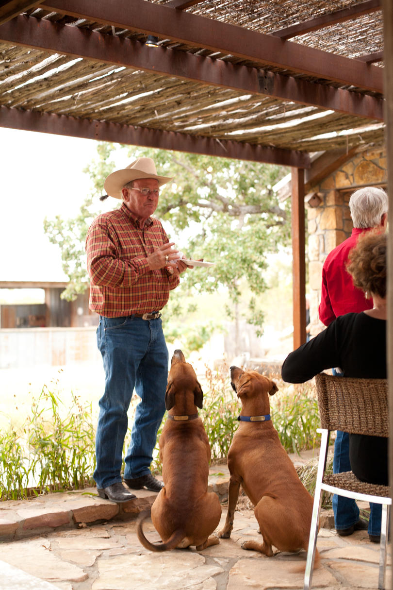 two dogs withing for man in cowboy hat to drop food