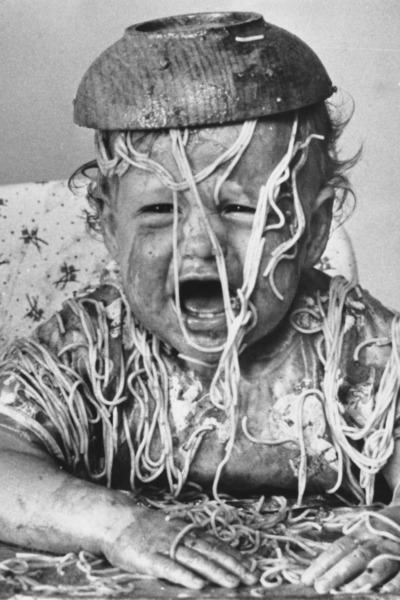 Baby covered in spaghetti with bowl on head