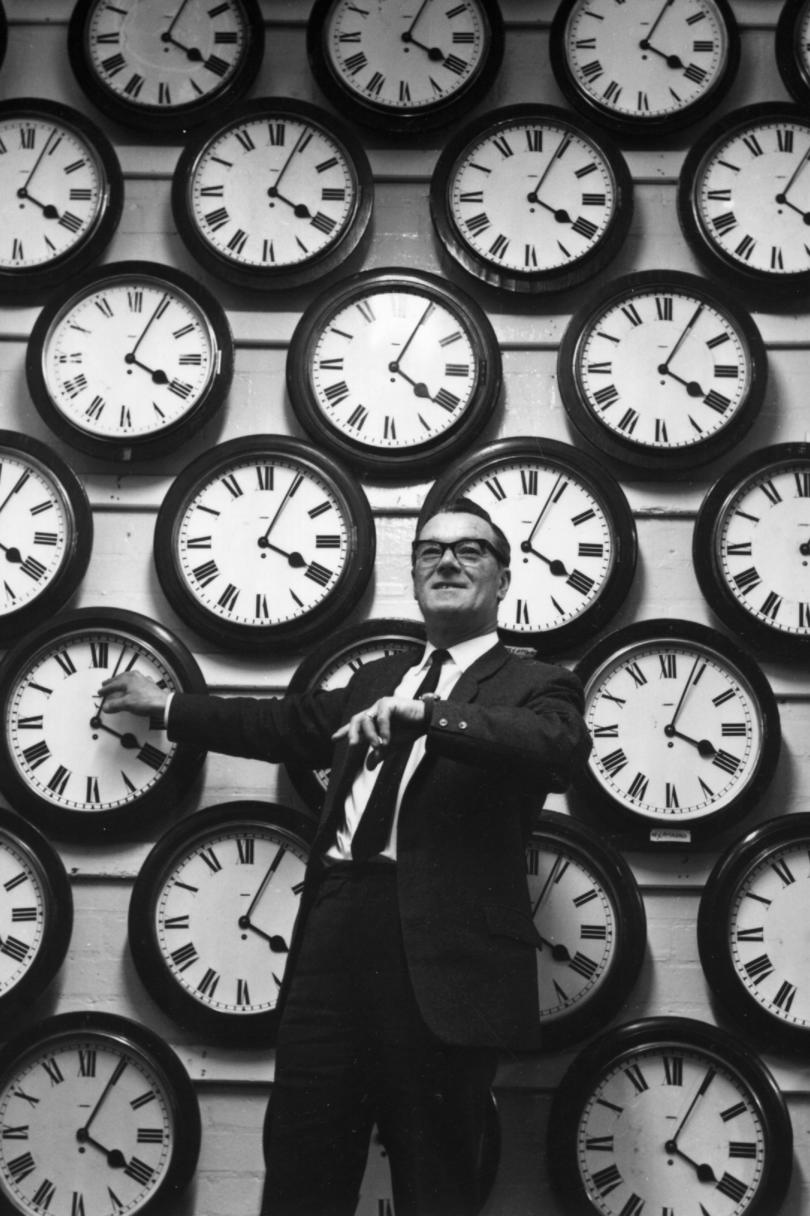 Man in Front of Wall of Clocks