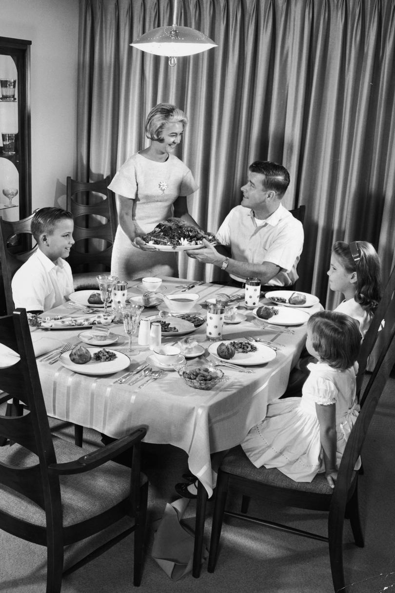 Woman Bringing Roast to Table for Family Dinner