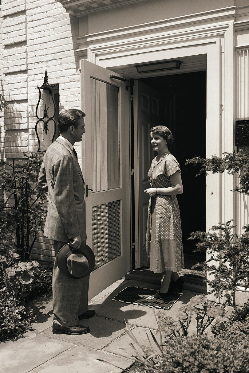 Woman Greeting Man at Front Door