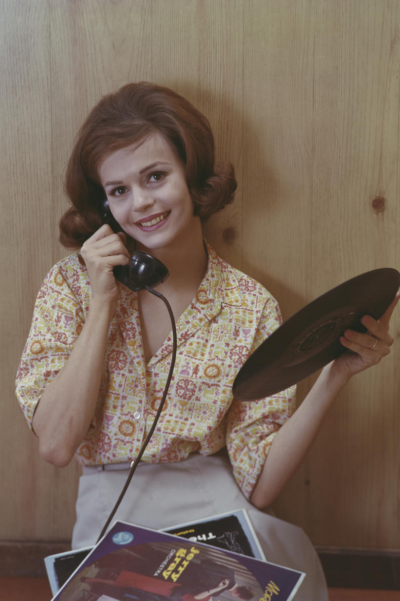 Woman Talking on Phone While Holding Records