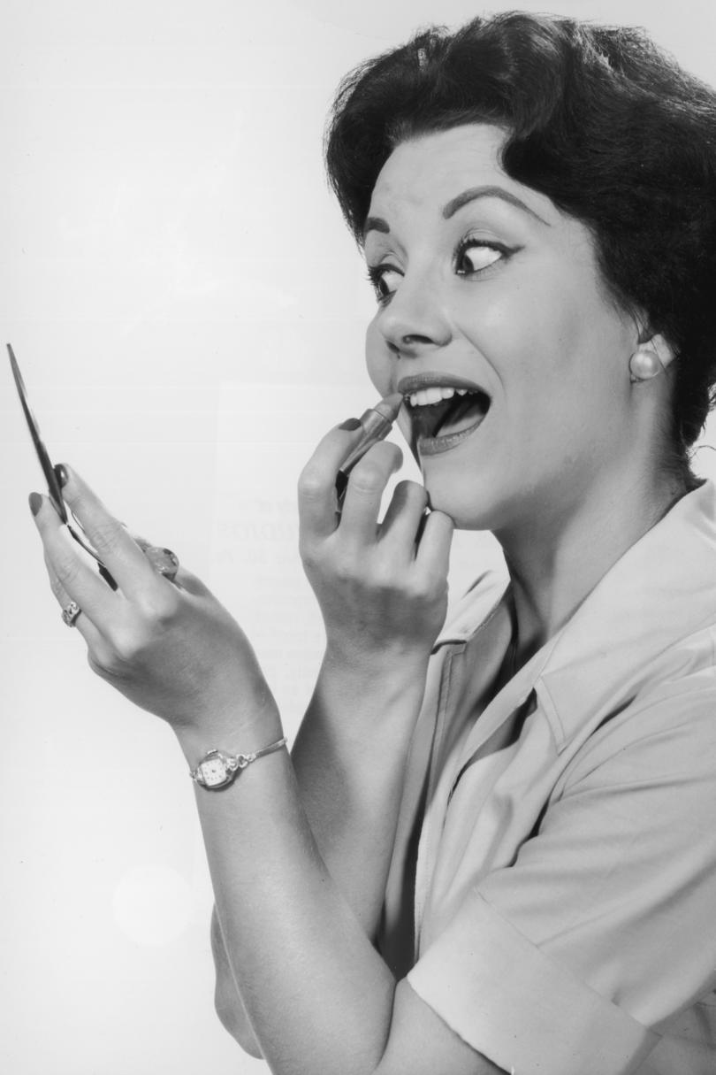 Woman applying lipstick with compact mirror