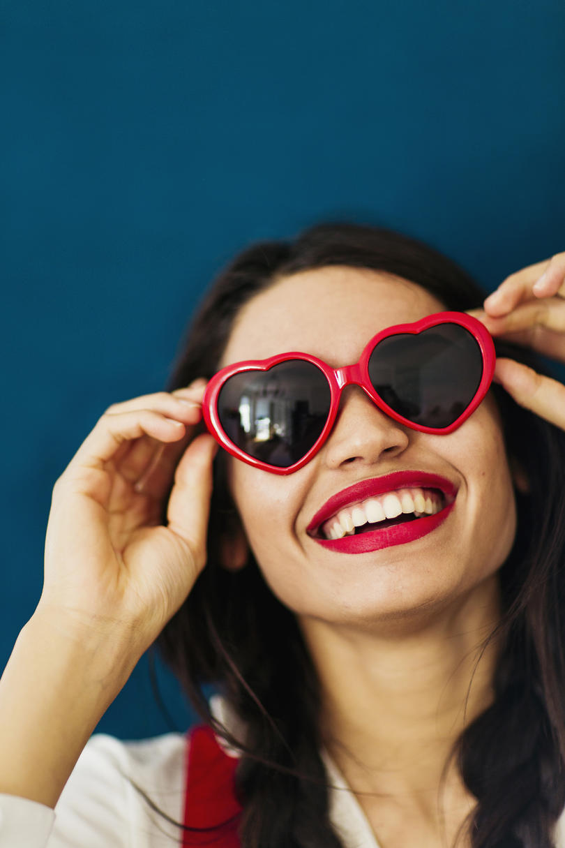 Woman with Red Lipstick and Heart Shaped Sunglasses Smiling
