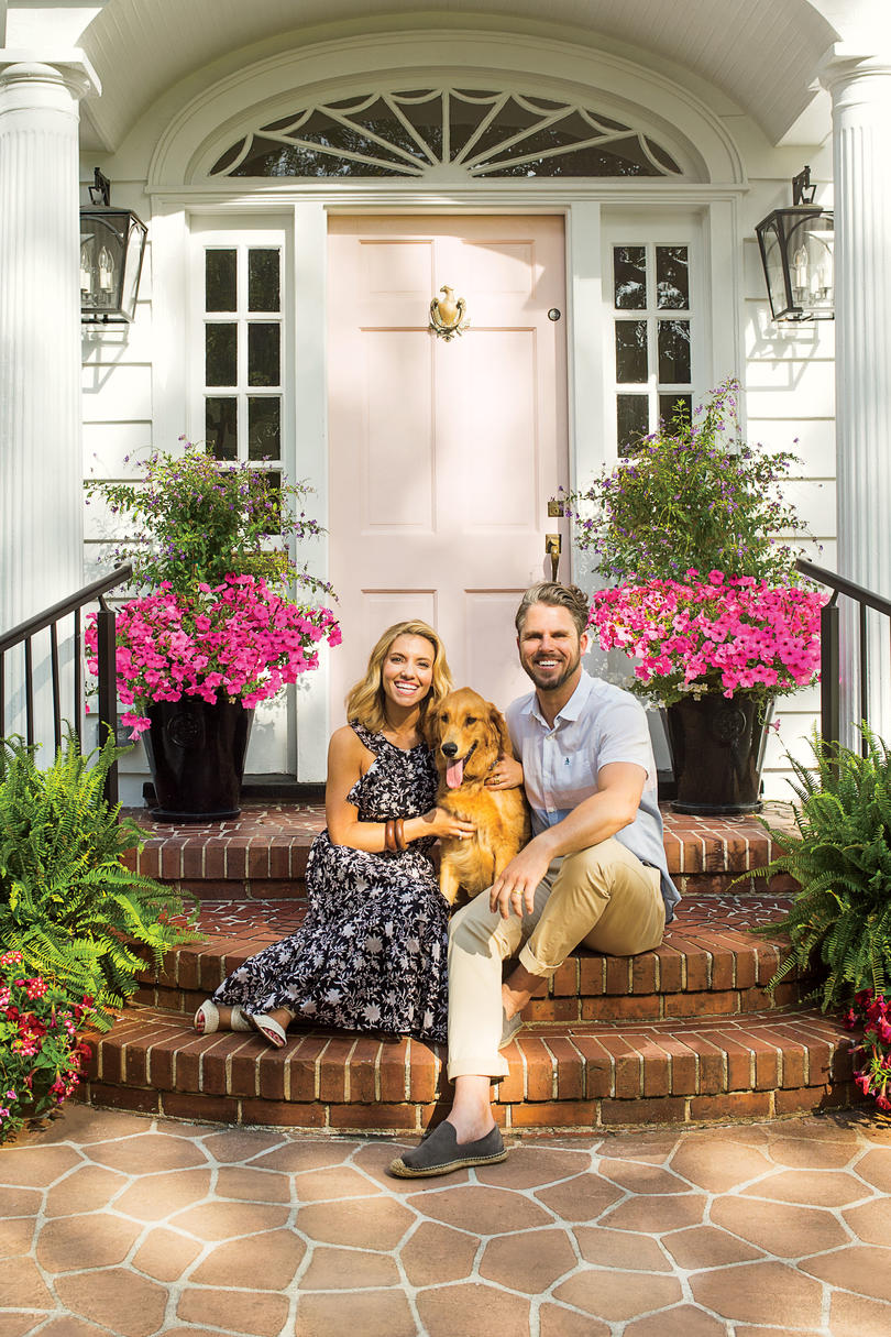 Lindsey and Grayson Cheek in front of their Wilmington, NC Home with a Pink Front Door