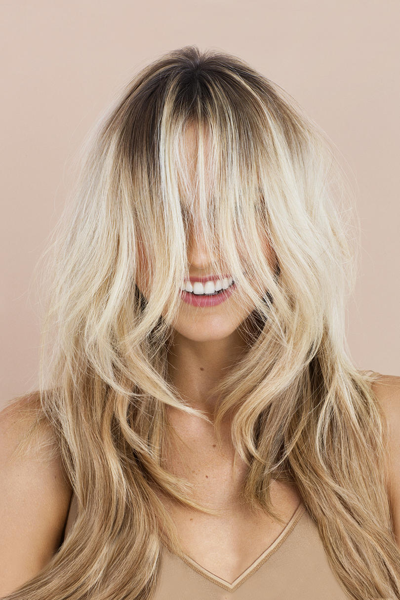 Model with blonde hair covering her face