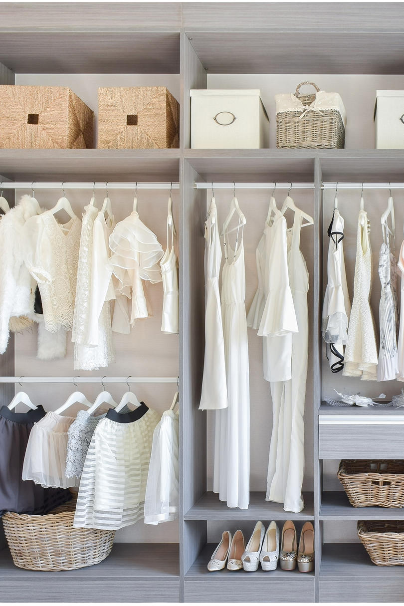 Pretty, minimal closet with bins on top shelf