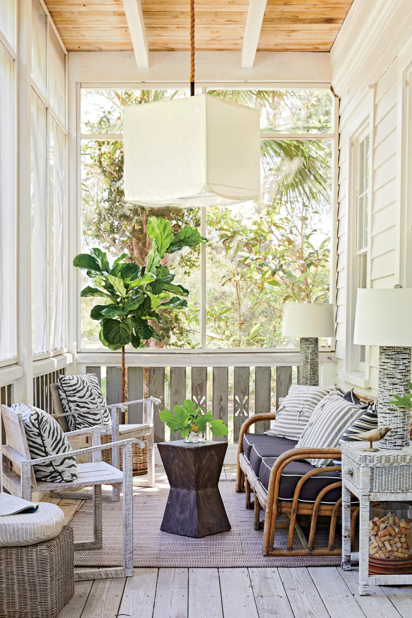 The ground-floor porch has character in spades: The sofa is vintage rattan, the chairs are crafted of whitewashed distressed barkwood, and the ceramic lamps are designed to resemble palm trunks.
