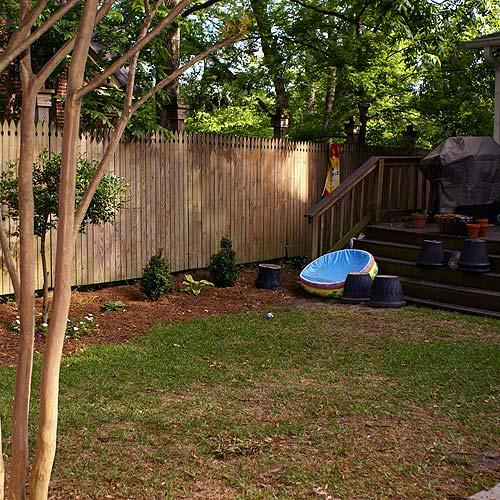 Blank wooden fence with toys nearby.