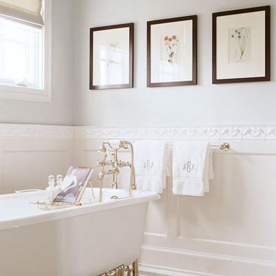 three, framed pictures are hung horizontally on the wall above a claw foot tub in