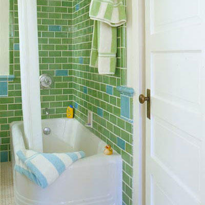 colorful green tiles (interspersed with light blue tiles) line the walls of a retro styled bathroom
