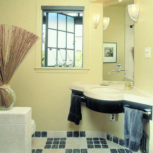 a new limestone vanity in the corner of the bathroom adds space, and exposing the sleek steel-framed window increases the natural light while a low wall at the end of the tub screens the toilet