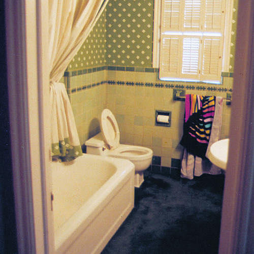Dark blue carpet and old green wallpaper darkened and enclosed an already tight area. The main fixtures -- the tub and toilet on one side, a pedestal sink and small cabinet on the other -- consumed the space.