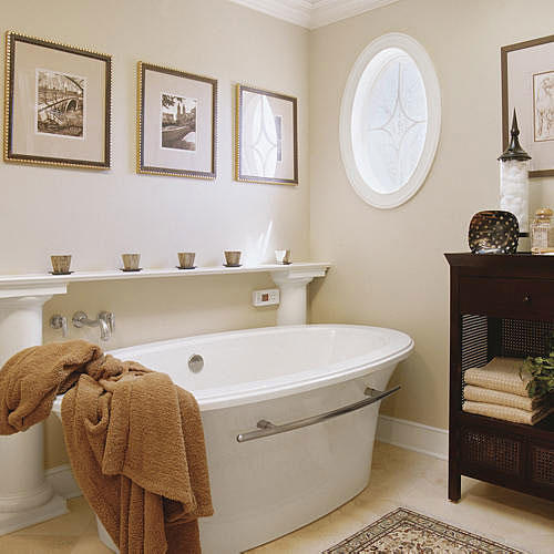 white, freestanding tub with a classic white shelf held up by neoclassical columns rises above the tub and an oval window with frosted glass pattern is on the wall across from the tub