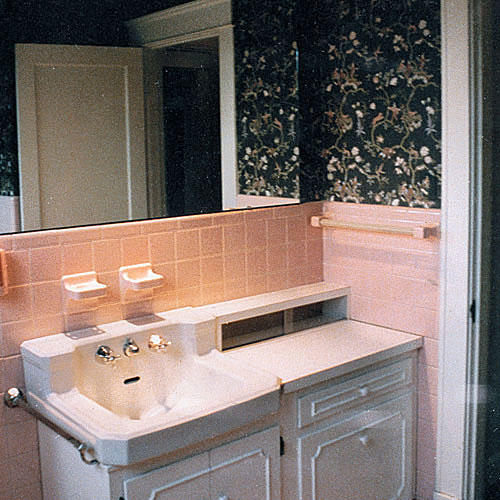 A Before Photo Of A Bathroom With Pink Tile Around The Sink Area And Dark,