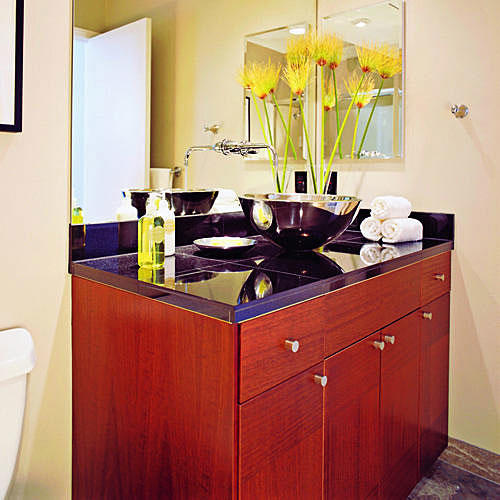 a stainless steel vessel sink sits on top of black granite sink counter top with cherry wood kitchen-cabinet base below in this teen's bathroom