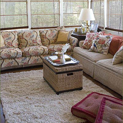 Couches are against the windows of the living room while a white, plush carpet rug is laid in the center of the room--which creates more space for children to play in the living room.