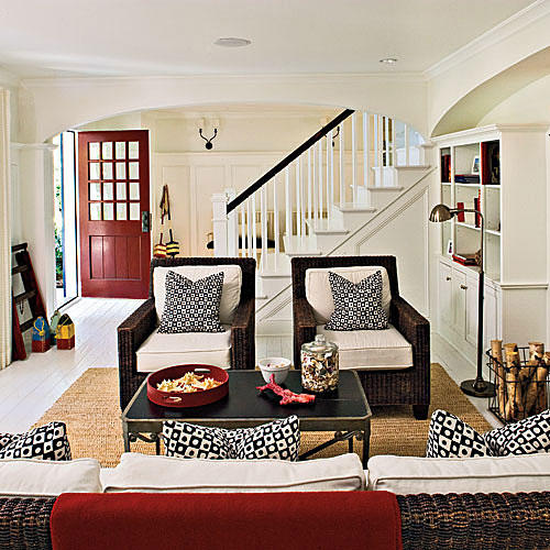 black and white graphic print plush cushions are arranged in the living room's wicker arm chairs while white walls brighten up the overall lighting of the living room