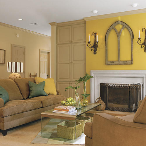 Yellow Walls Highlight The Artwork Above Family Room Fireplace While Couch Faces A Clear