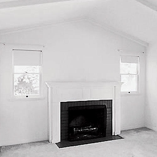 empty 1940s living room with a fireplace that has two narrow windows on each side
