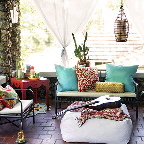 front porch with porch furniture (love seat and chairs with white cushions, colorful, red side table and a white bean bag in the middle with a guitar on top)