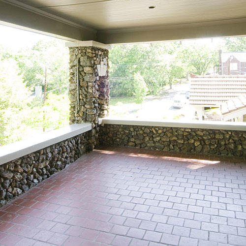 bare front porch with red tile and a stone ledge around the perimeter