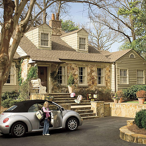 driveway with parking spaces set in front of the home with stone steps leading directly up to the front door