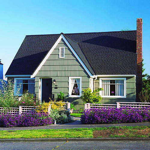 purple flowers line the front of a white fence with yellow flowers lining the front of the house
