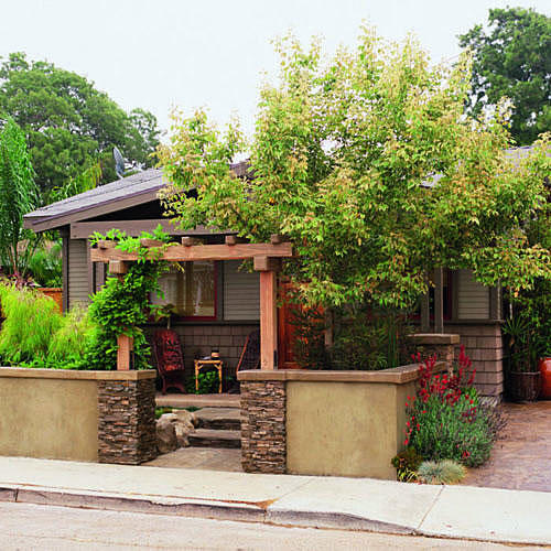 bungalow home with a large bush in front and a low wall around the front of the yard