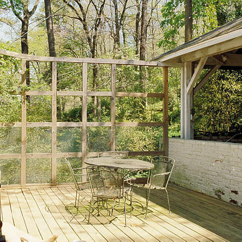 old backyard deck with wooden square scaffolding on the edge and outdoor table and chairs
