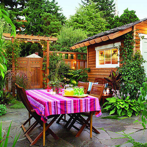 bright and colorful backyard with a striped tablecloth over an outdoor table with a wooden garden shed, in the background