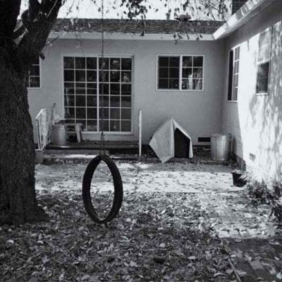 before photo of a backyard with a tire swing and a large tree
