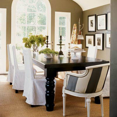 classic and stylish dining room with a large black table with white, slip-covered chairs surrounding it and a striped arm chair at the head of the table