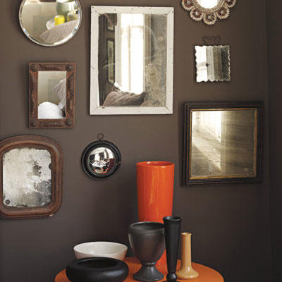 framed mirrors of various sizes hung on a dark, brown wall with an orange circular table with various sized vases arranged on top