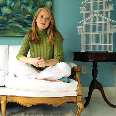 homeowner sitting cross-legged on a white loveseat in front of turquoise walls with a white birdhouse on small end table
