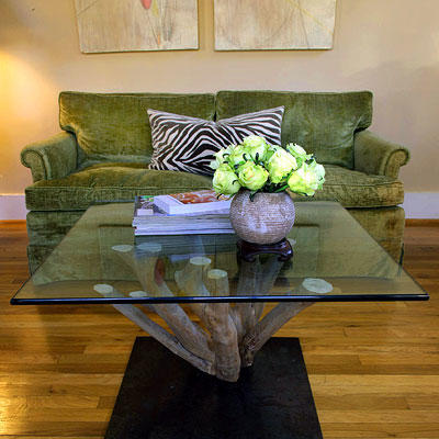 coffee table made out of the base of a crepe myrtle with a  glass top facing in front of a green couch with a zebra pillow