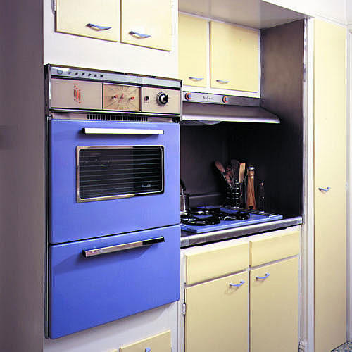 In this kitchen update, periwinkle paint covers a kitchen oven and stovetop while the cabinets' doors are painted a pale yellow color with rest covered in creamy white.