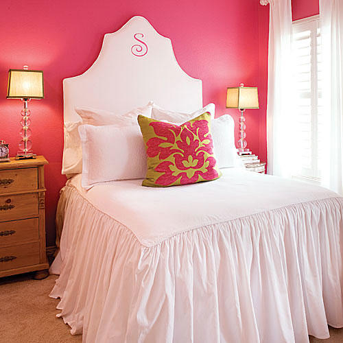 bright pink-coral paint on the wall off-sets a white, fabric headboard with a gathered comforter on the bed giving a tropical feel to the decor