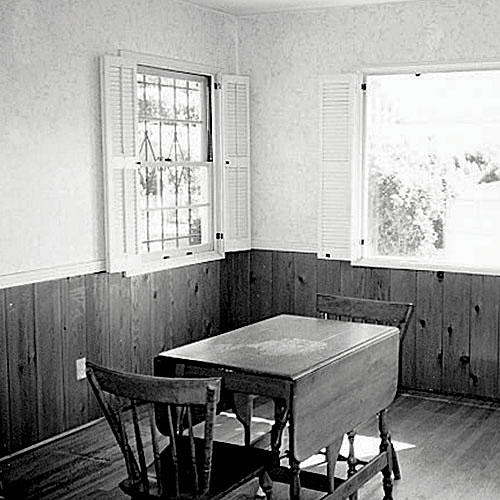 A before photo of a dining room with pine boards up half of the wall that has windows with interior shutters. A small table with two chairs is positioned in the middle of the room.