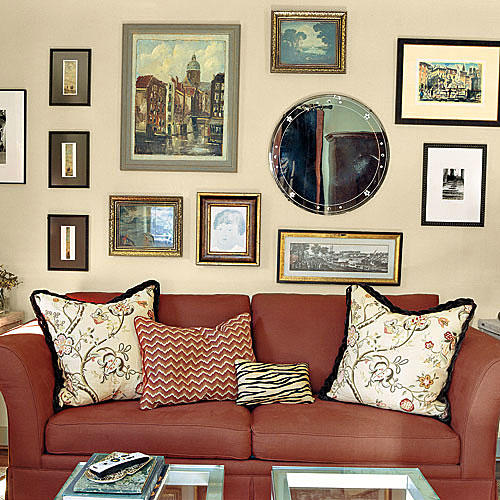 family room wall with gallery layout of framed prints, paintings and mirrors hung over a red couch with pillows
