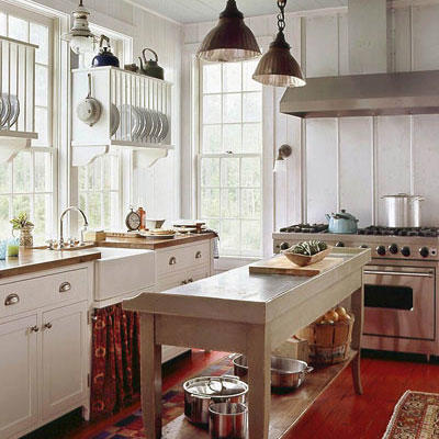 Light and bright airy kitchen with windows along the left side, over the sink area and in the middle of the kitchen, a long prep table with room for storage underneath. Also a stainless steel gas/oven range is a the far end of the kitchen.