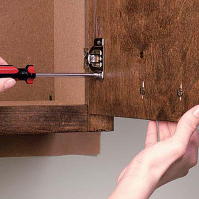 screwing in a door hinge inside a kitchen cabinet