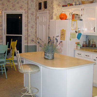 outdated kitchen with a white kitchen island and a bar stool pulled up to it