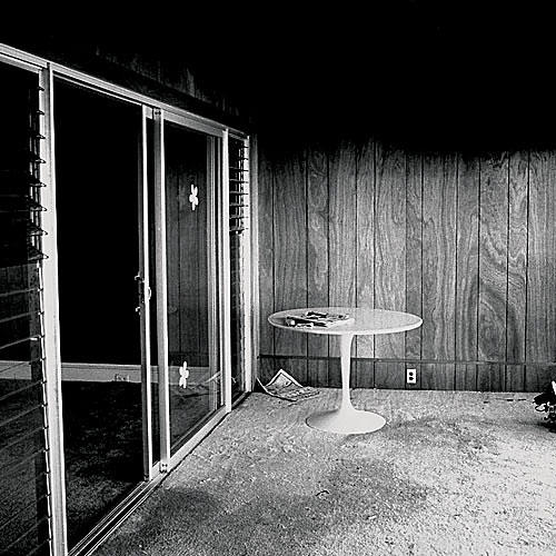 wood paneling in a carpeted room with a round white table and a sliding glass door to the left side