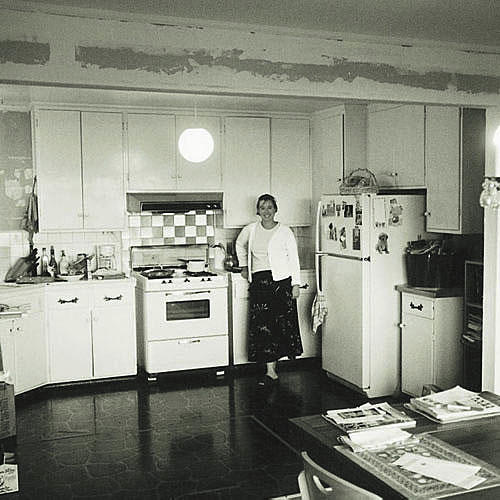 outdated kitchen with plain white cabinets, dark floors and an old white stove