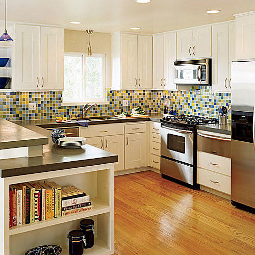 bright, blue, yellow, blue and brown tile splash gives the kitchen remodel a vivid design and makes the modern, white cabinets pop against the stainless steel refrigerator, stove and microwave