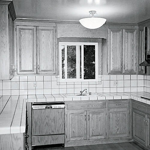 outdated kitchen with a u-shaped layout and tile countertop