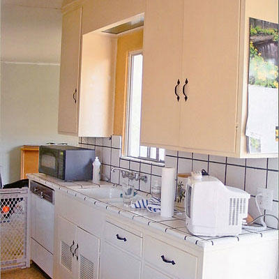 kitchen with peach cupboards above the sink and white cupboards below with white tile backsplash and tile counters