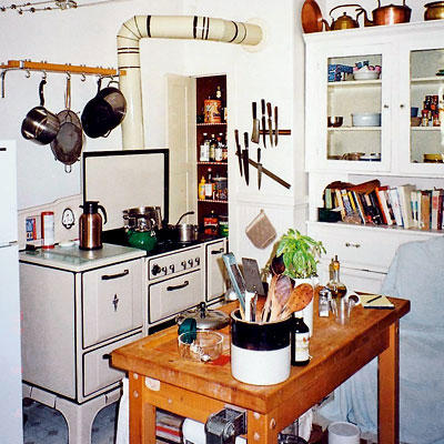 turn of the century stove in an outdated kitchen with a tall cabinet